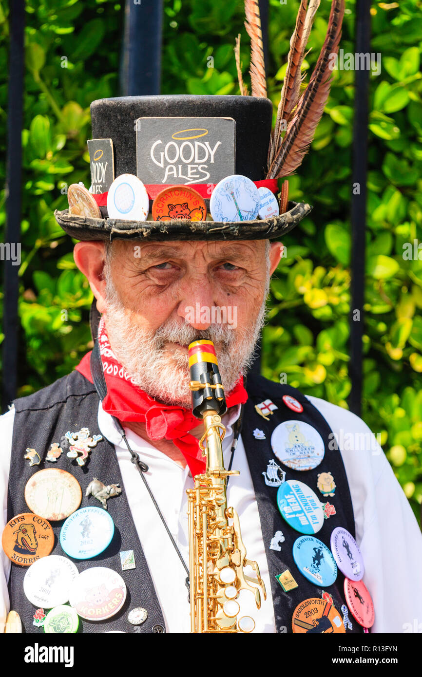 Braodstairs Folk Week. Morris man musician facing viewer, with eye-contact, playing saxophone. Black costume decorated with many event badges. - Stock Image