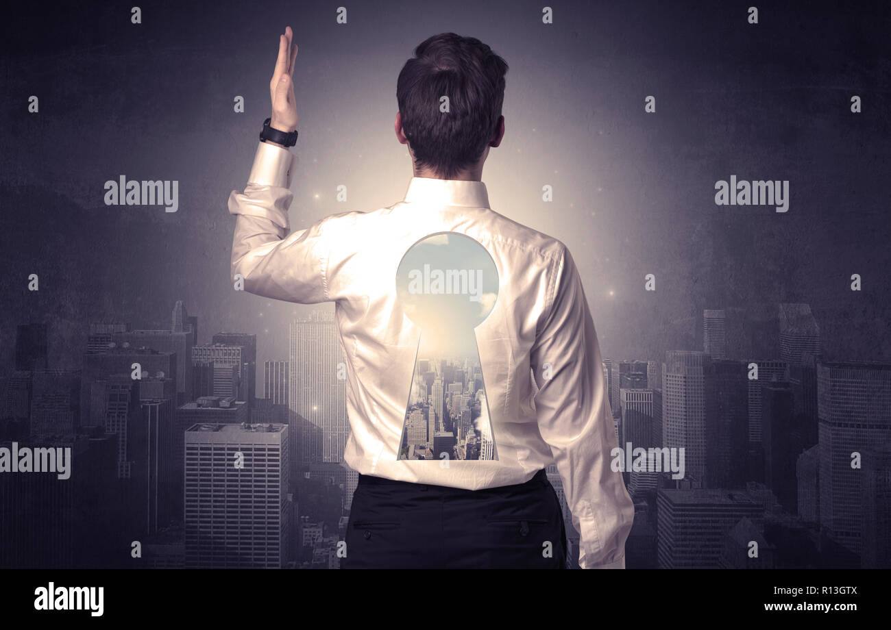 Young businessman standing and thinking with keyhole on his back and city graphic around - Stock Image