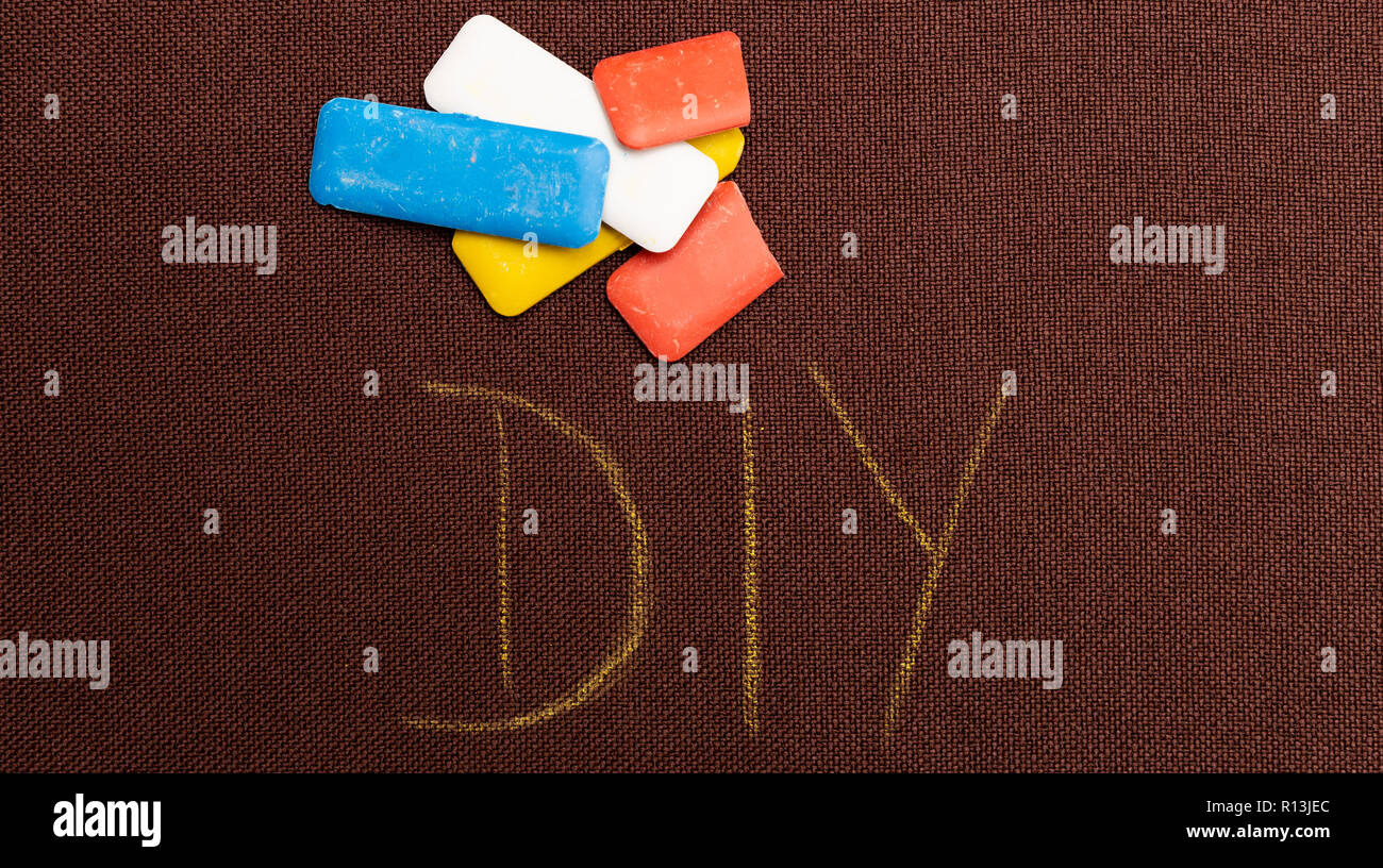 DIY as do it yourself concept being written on brown material with coloured tailoring chalk above - Stock Image