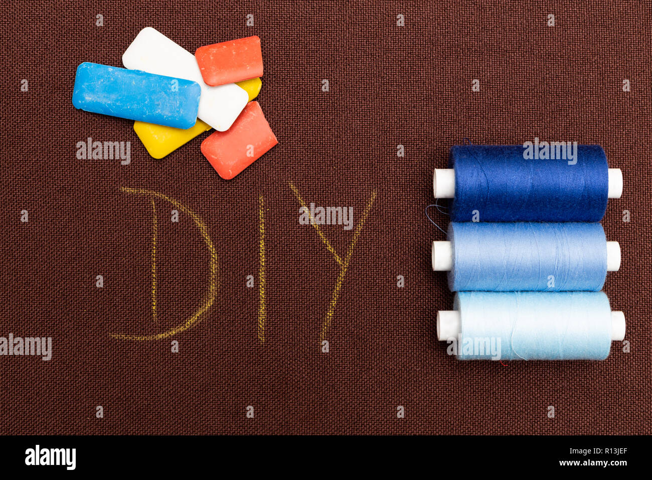 Brown material DIY as do it yourself concept written on it with coloured chalk and shades of blue thread spools nearby - Stock Image