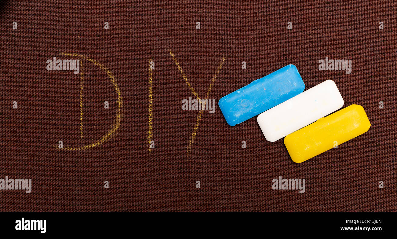 DIY as do it yourself concept written on brown fabric as background next to coloured tailoring chalk - Stock Image