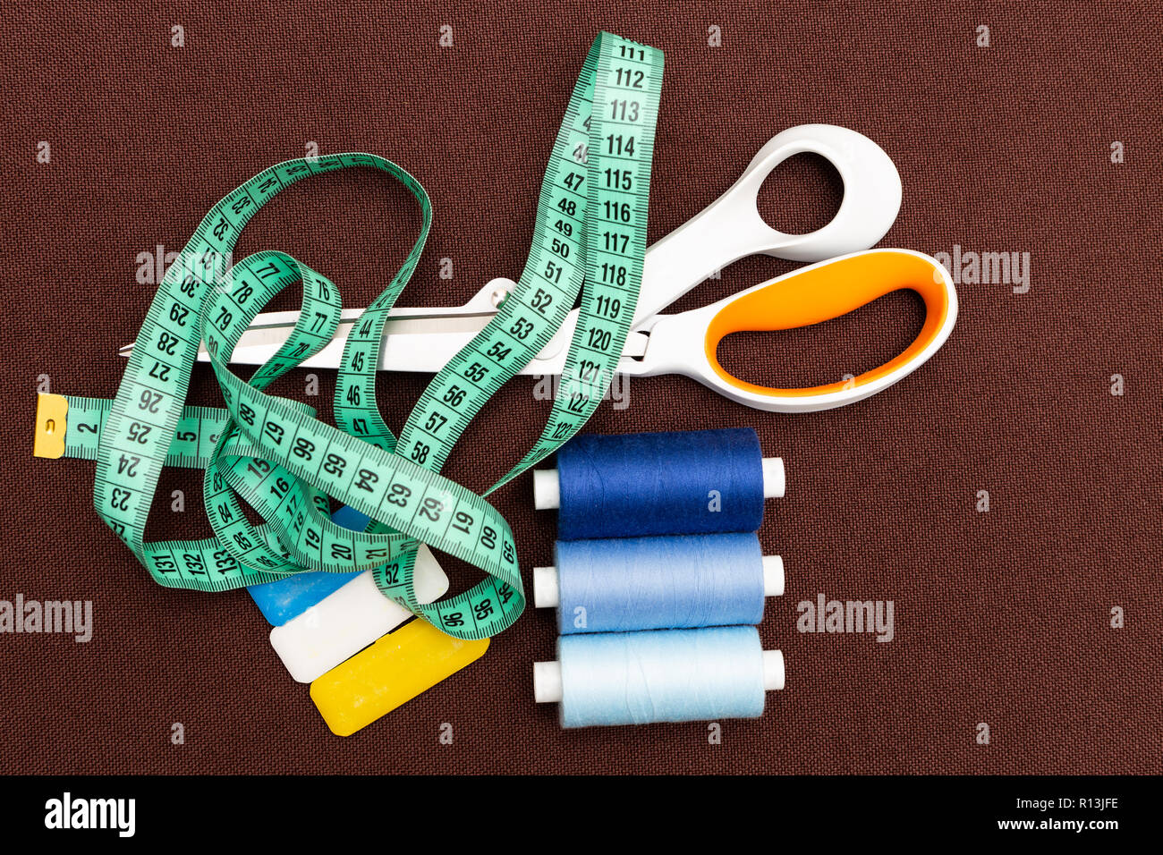 Equipment for sewing such as scissors, thread, chalk and measuring tape on brown fabric background - Stock Image