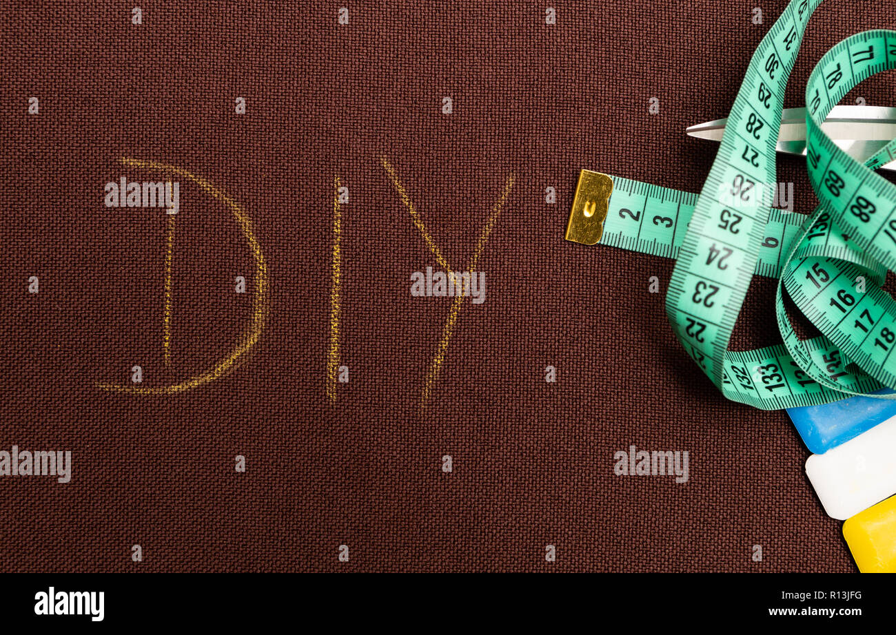 DIY text as do it yourself or handmade concept written on brown fabric as background with scissors, measuring tap and chalk - Stock Image
