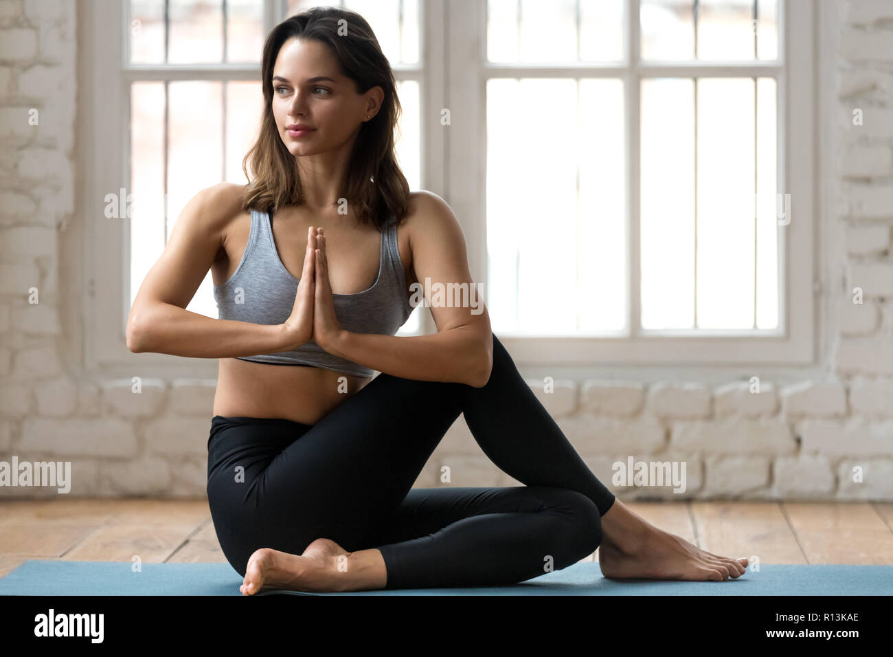 Young woman practicing yoga, doing Ardha Matsyendrasana pose - Stock Image