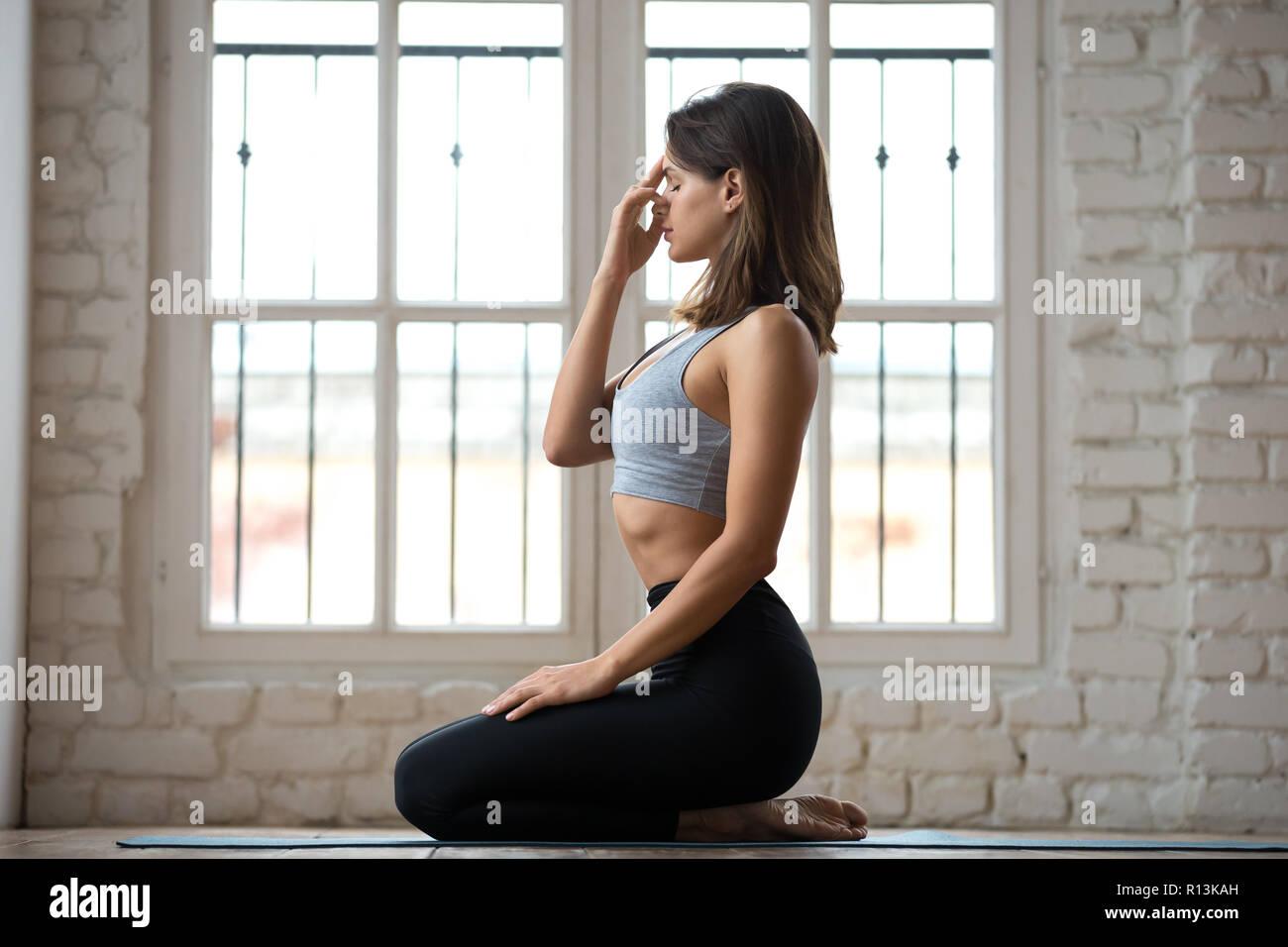 Young sporty woman practicing yoga, nadi shodhana pranayama