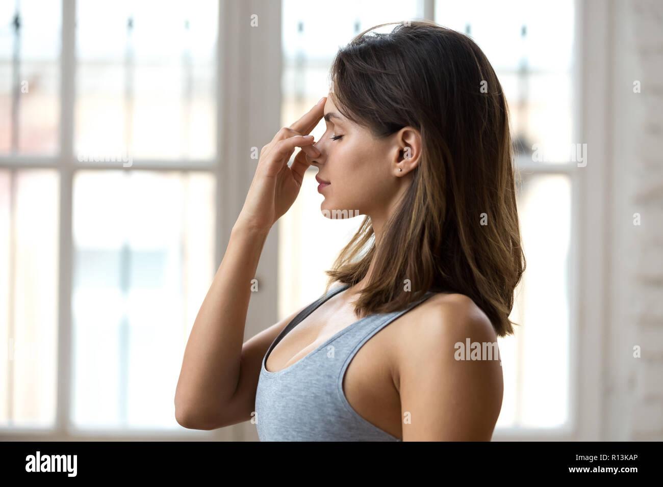 Young woman practicing yoga, nadi shodhana pranayama pose