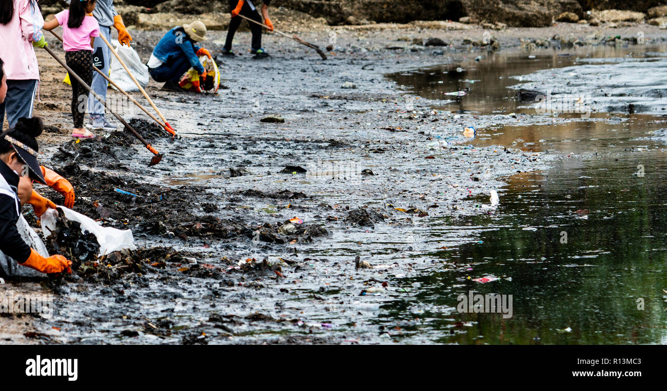 Adult and children volunteers collecting garbage on the sea beach. Beach environment pollution. Tidying up rubbish on beach. People wear orange gloves - Stock Image