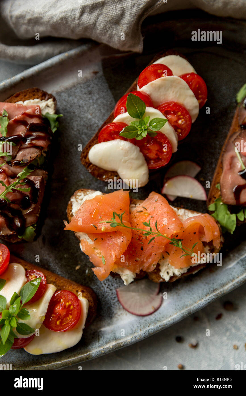 Sandwiches with roast beef and arugula, salmon and cumin, mozzarella and tomatoes on brown bread at gray plate Stock Photo
