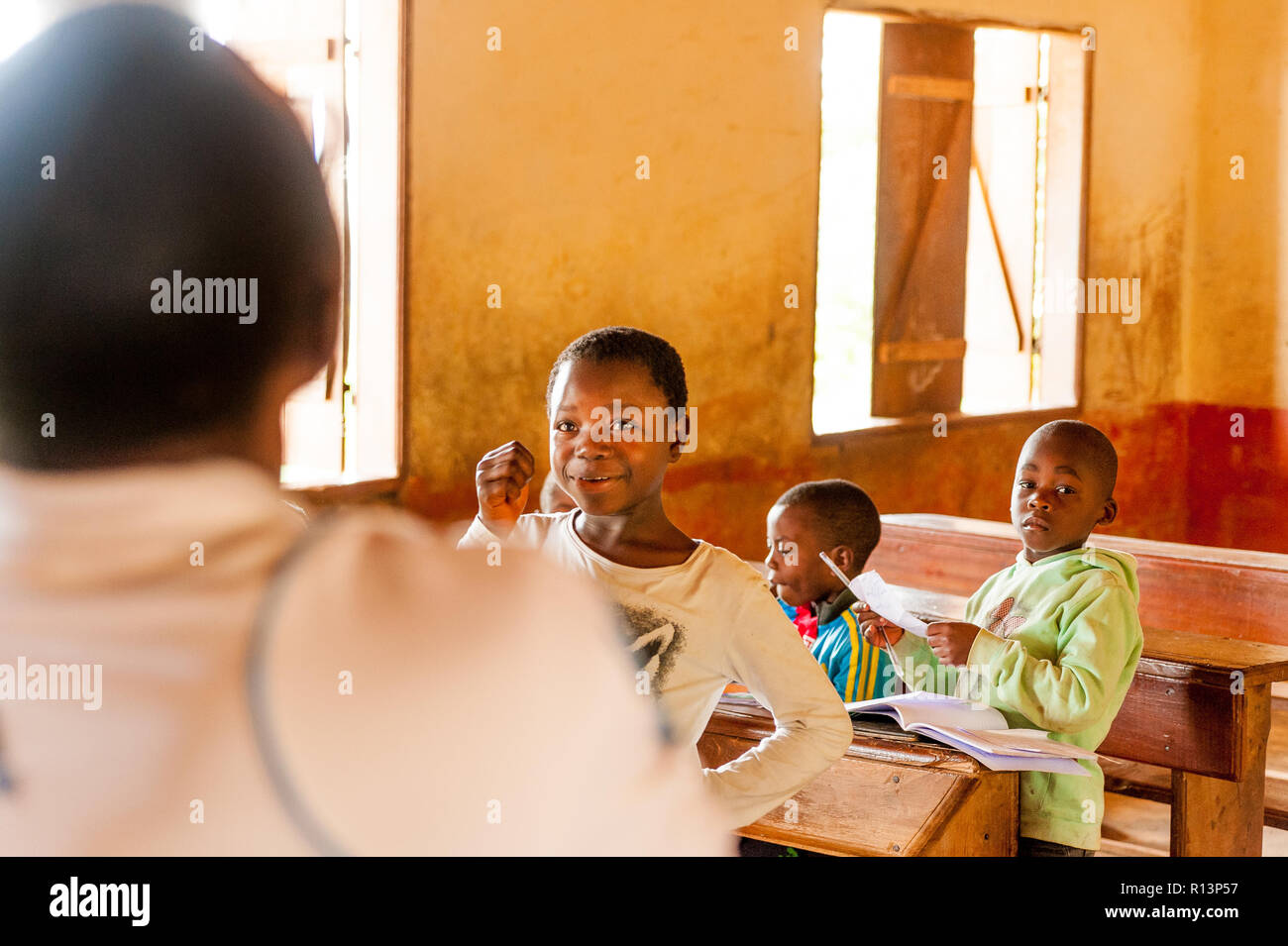 Bafoussam, Cameroon - 06 august 2018:  smiling school girl during lesson in village school talking with teacher Stock Photo