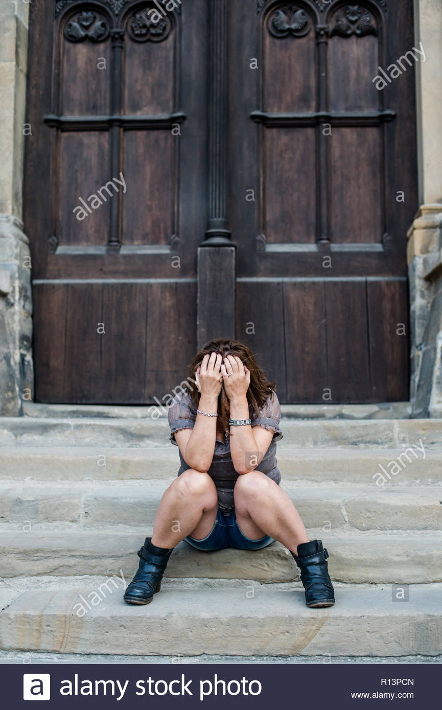 Midsection of a woman sitting on steps - Stock Image