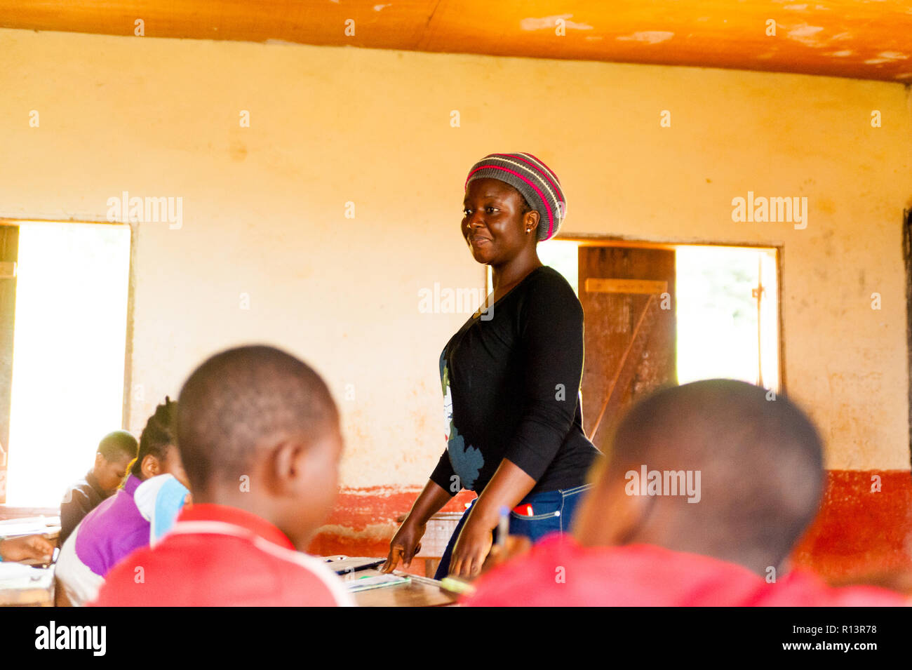 Bafoussam, Cameroon - 06 august 2018: young african girl teacher volunteer smiling during lessonstanding up among children Stock Photo