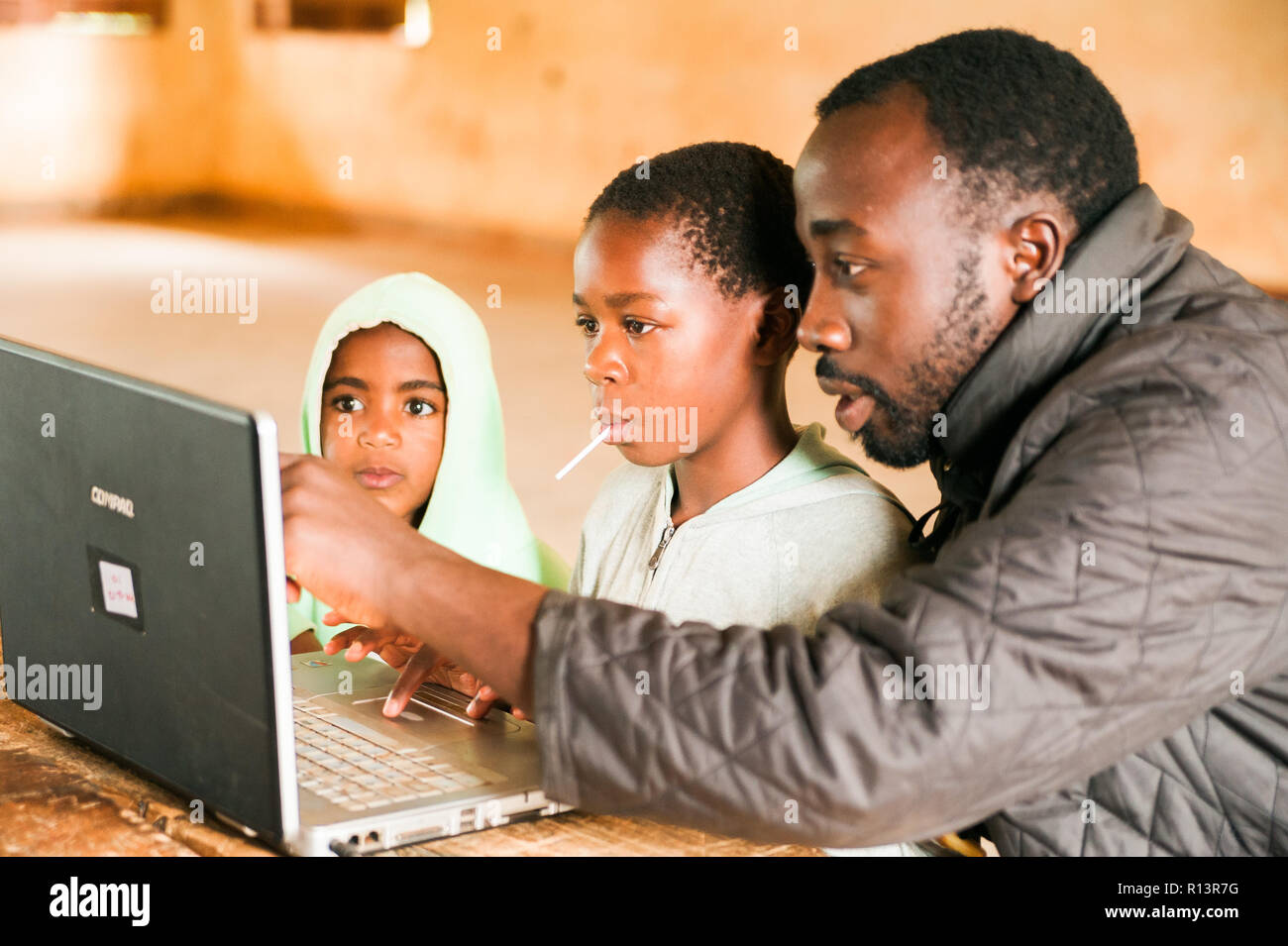 Bafoussam, Cameroon - 06 august 2018: young african children learn to use computer with young teacher touching screen Stock Photo