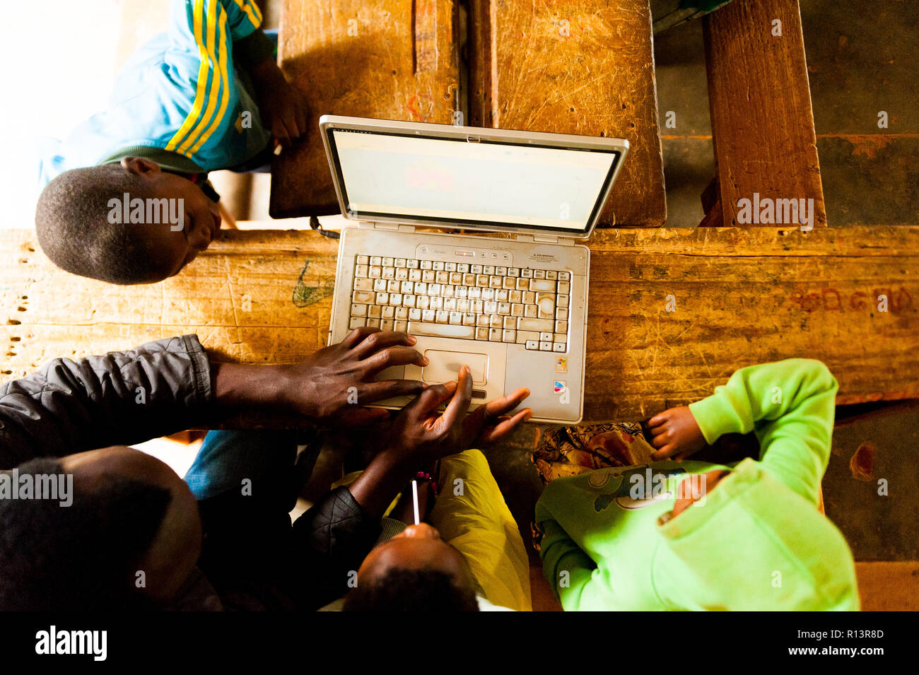 Bafoussam, Cameroon - 06 august 2018: above view of african kids and teacher teaching how to use laptop to increase development Stock Photo