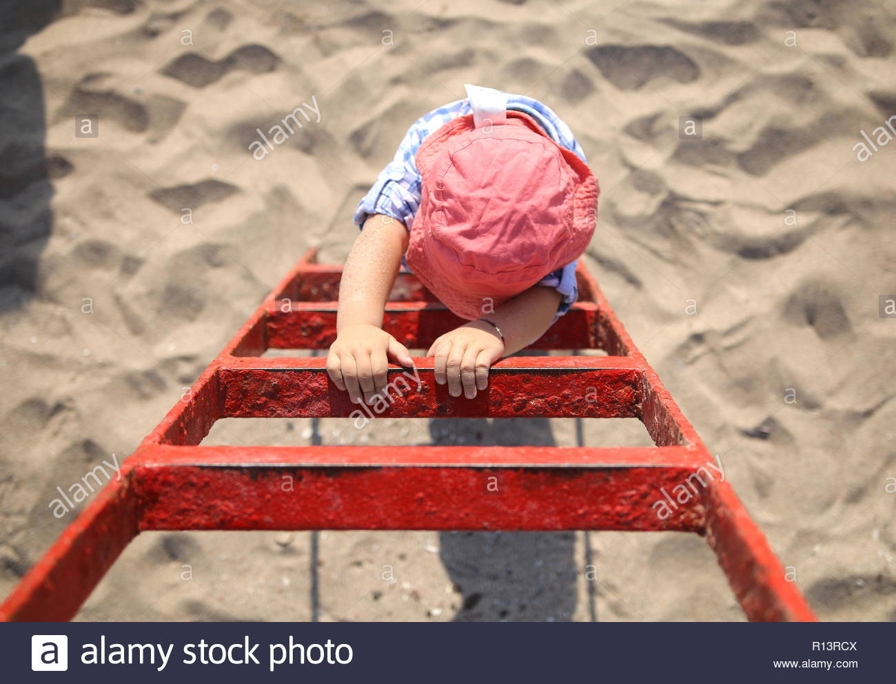 High angle view of a child playing in the sand at the beach - Stock Image