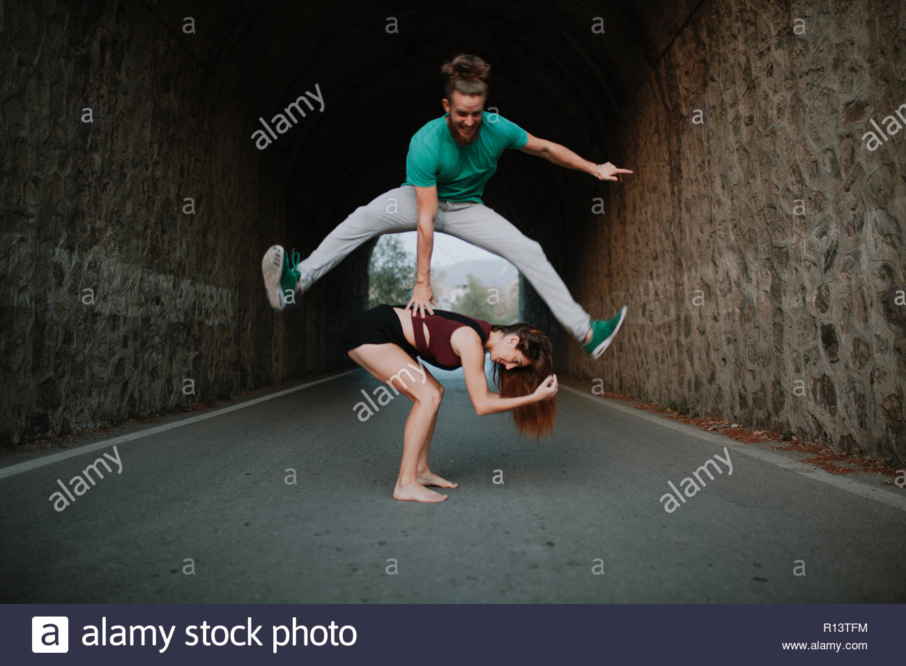 A young couple doing action shots in the street - Stock Image