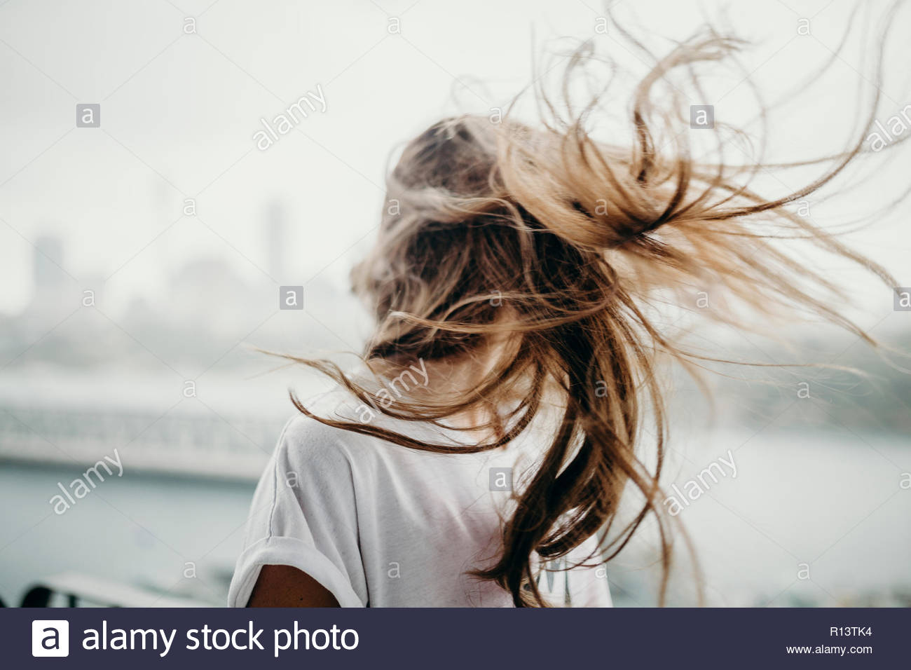 Action shot of a girl tossing her hair back - Stock Image