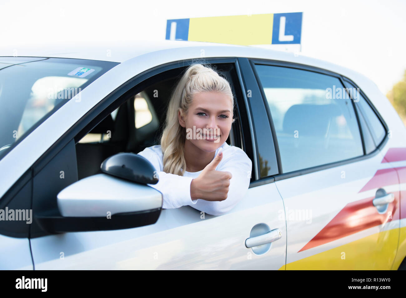 Driving school. Female young car driver going thumbs up after passing the driving license test. Successful woman smiling in vehicle. Free space for te Stock Photo