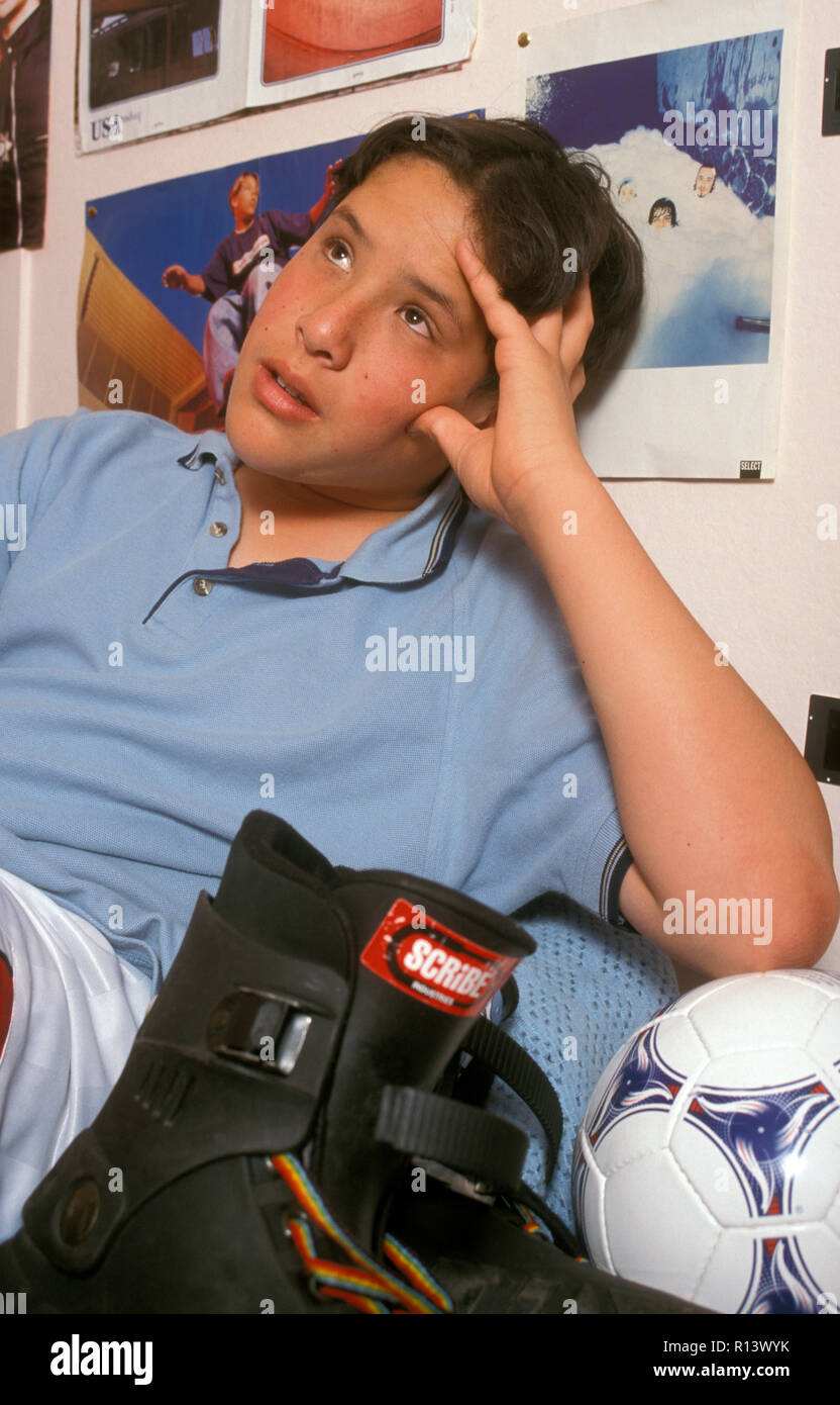spaced out teenage boy sitting in his bedroom next to rollerblades Stock Photo