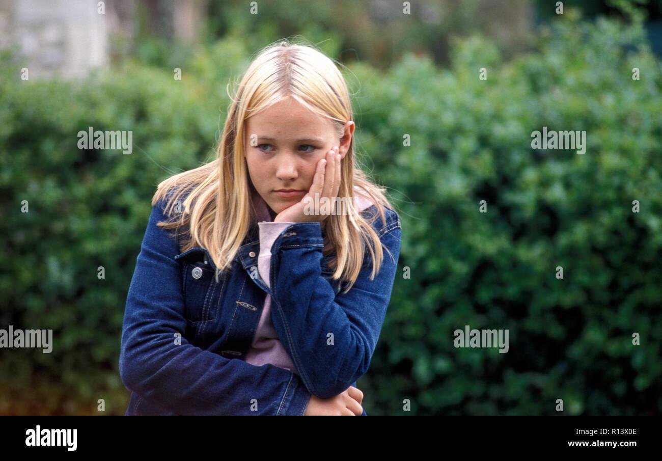 unhappy teenage girl sitting alone outside - Stock Image
