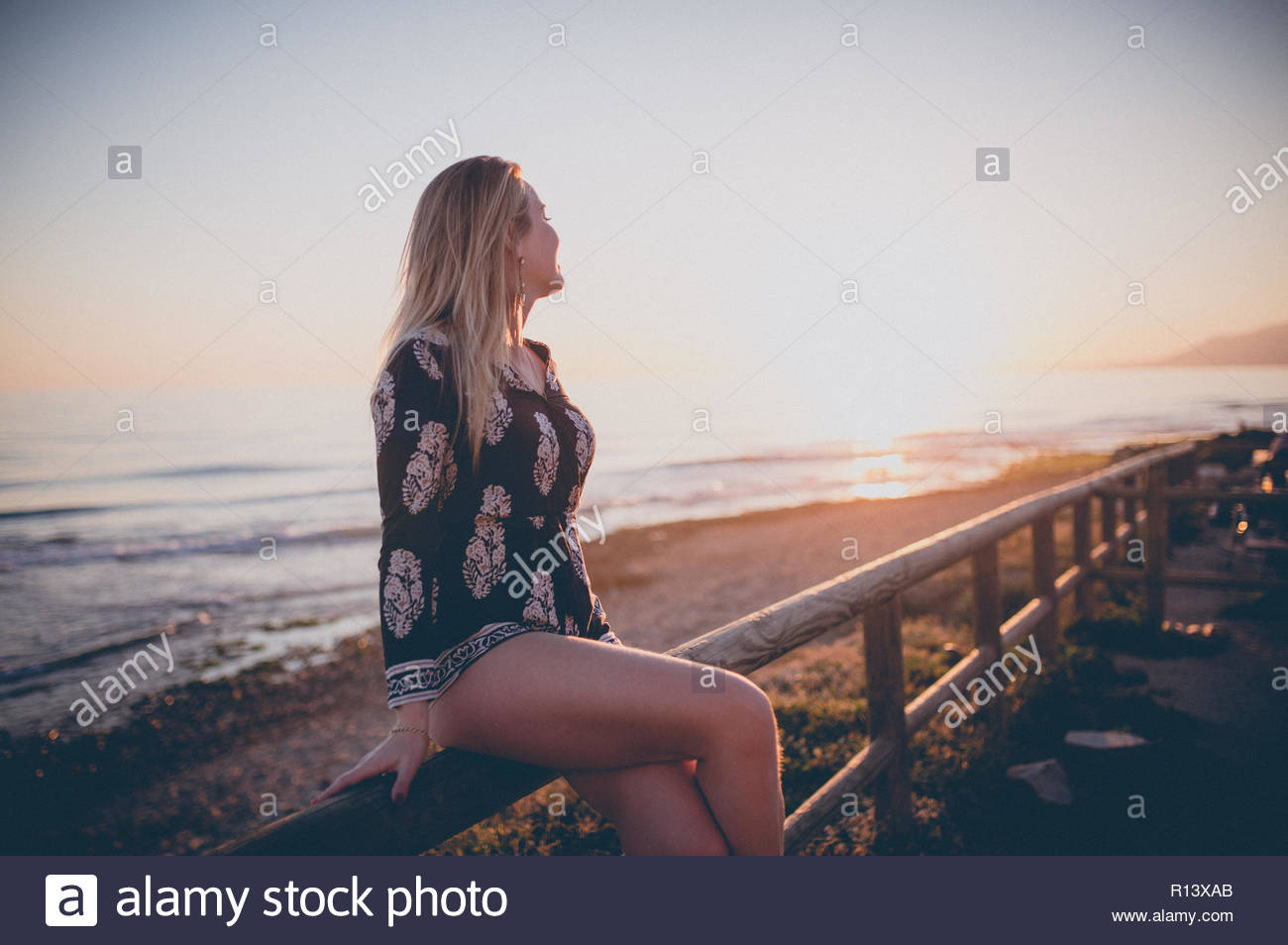 A woman looking out at sea during sunset - Stock Image