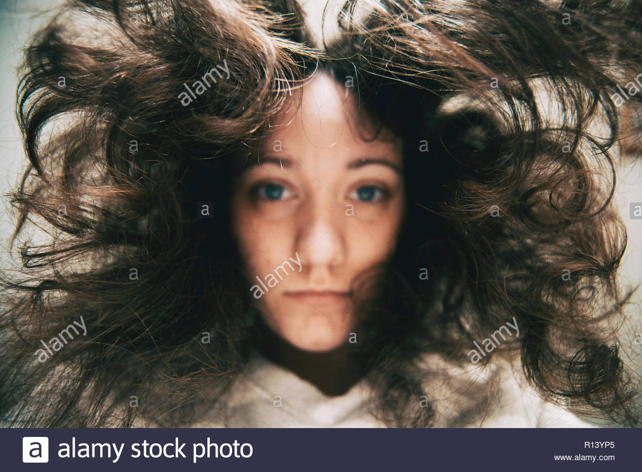 A woman looking into the camera under water - Stock Image