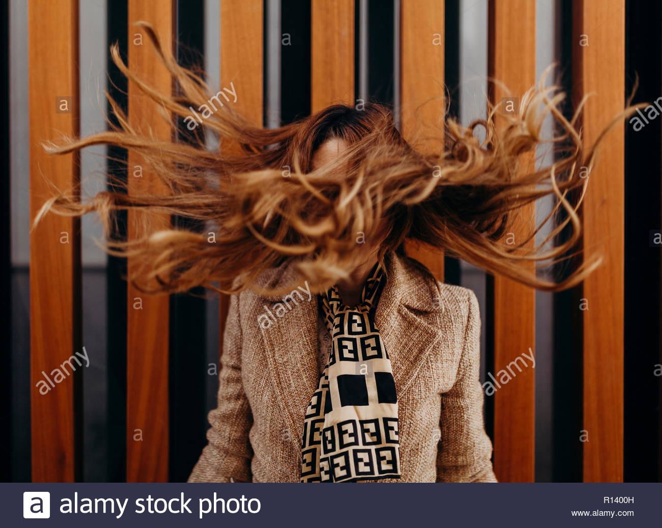 Portrait of a woman tossing her long hair - Stock Image