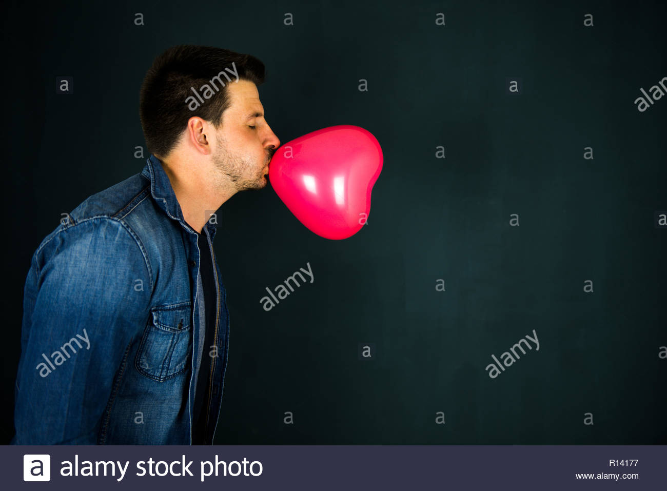 Side view of a young man blowing up a red balloon - Stock Image