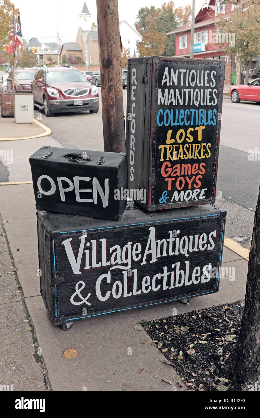 Village Antiques and Collectibles display on a sidewalk outside the shop on the main street in downtown Sugarcreek, Ohio, USA. - Stock Image