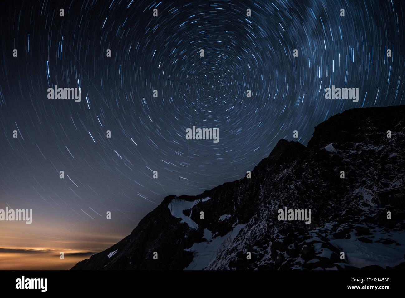 Night sky star trails above Aiguille de Bionnassay mountain, Alps, France Stock Photo
