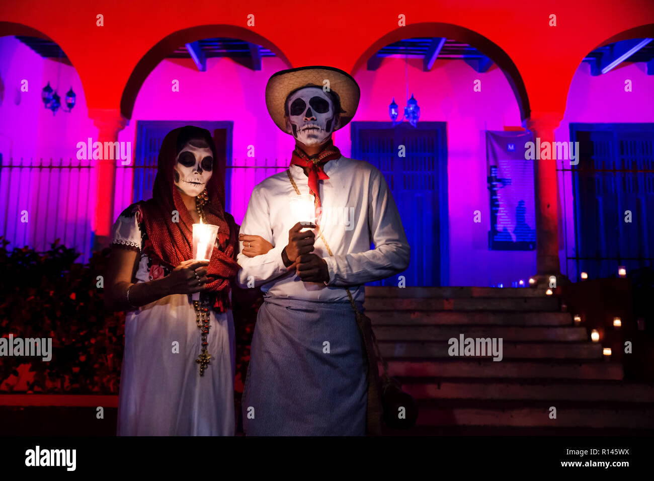 Merida, Cementerio General, Mexico - 31 October 2018: Close up of customed man and woman with with mexican traditional white clothes and skull make-up Stock Photo