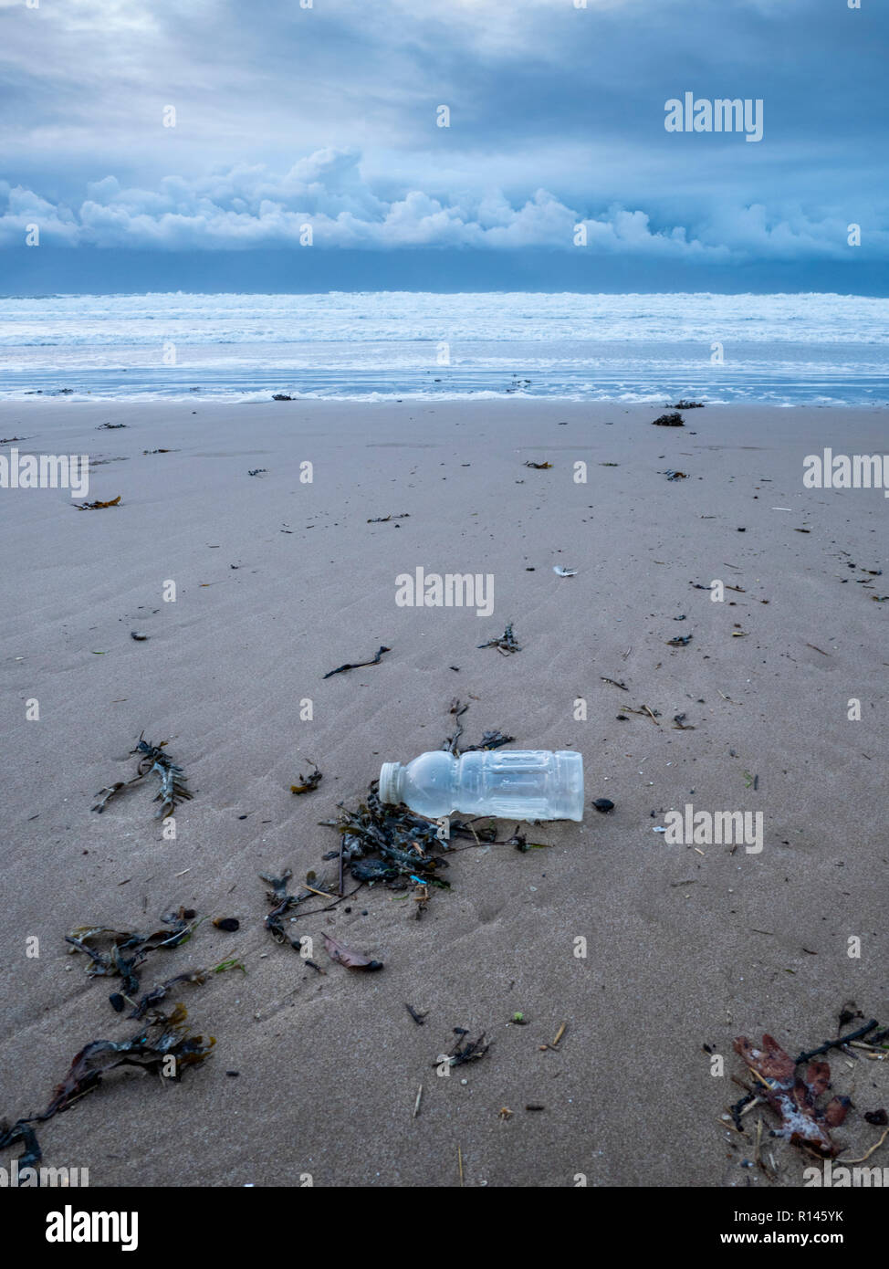 A discarded plastic bottle on a beach in the UK part of the plastic pollution and environmental problem - Stock Image