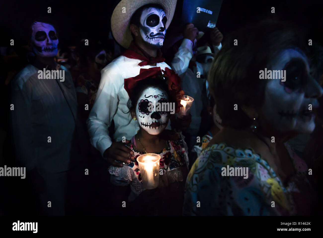 Merida, Cementerio General, Mexico - 31 October 2018: Customed participants of the parade with skull make-up, with a cowboy man and kid with flowers a - Stock Image