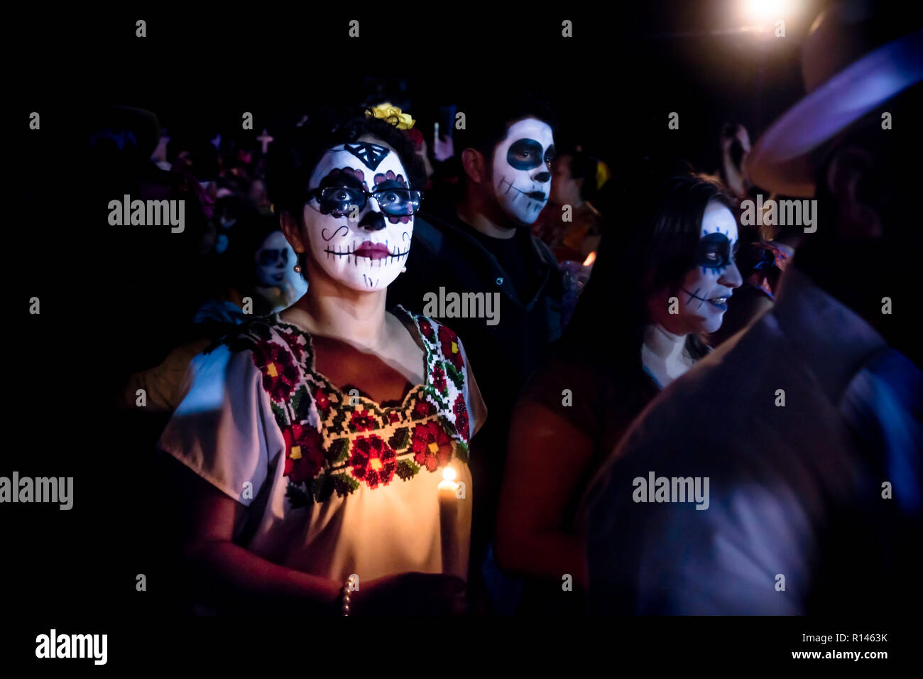 Merida, Cementerio General, Mexico - 31 October 2018: Woman with skull and spiderweb make-up and glasses and dress with traditional mexican flowers su Stock Photo