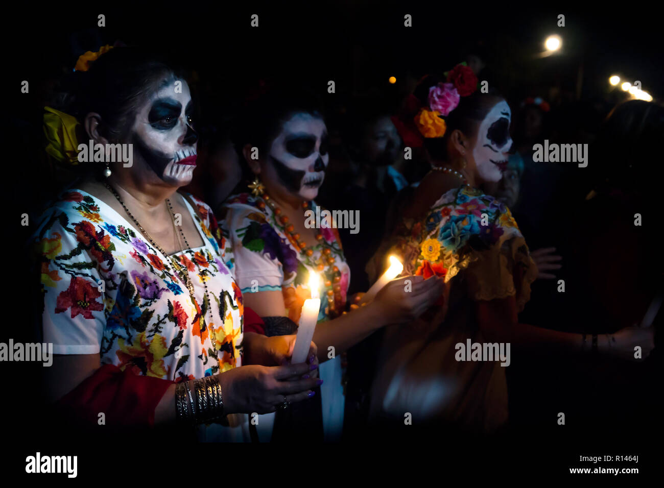 Merida, Cementerio General, Mexico - 31 October 2018: Three customed woman dressed as Catrinas with skull make-up having troubles with the candles bet - Stock Image