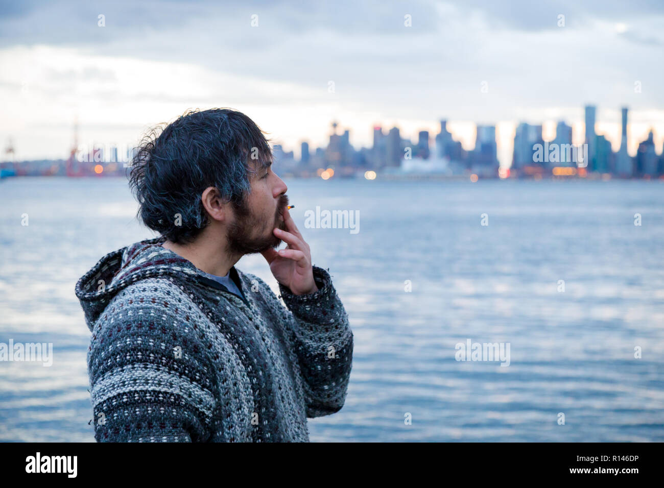 A young man smoking a joint with downtown Vancouver, BC, in the background shortly after Canadian marijuana legalization. - Stock Image