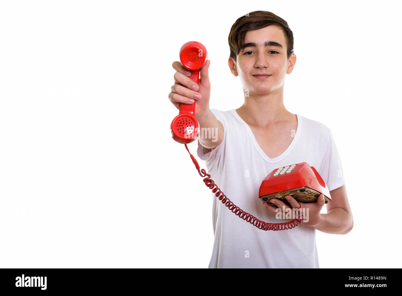 Studio shot of young handsome Persian teenage boy giving old tel - Stock Image