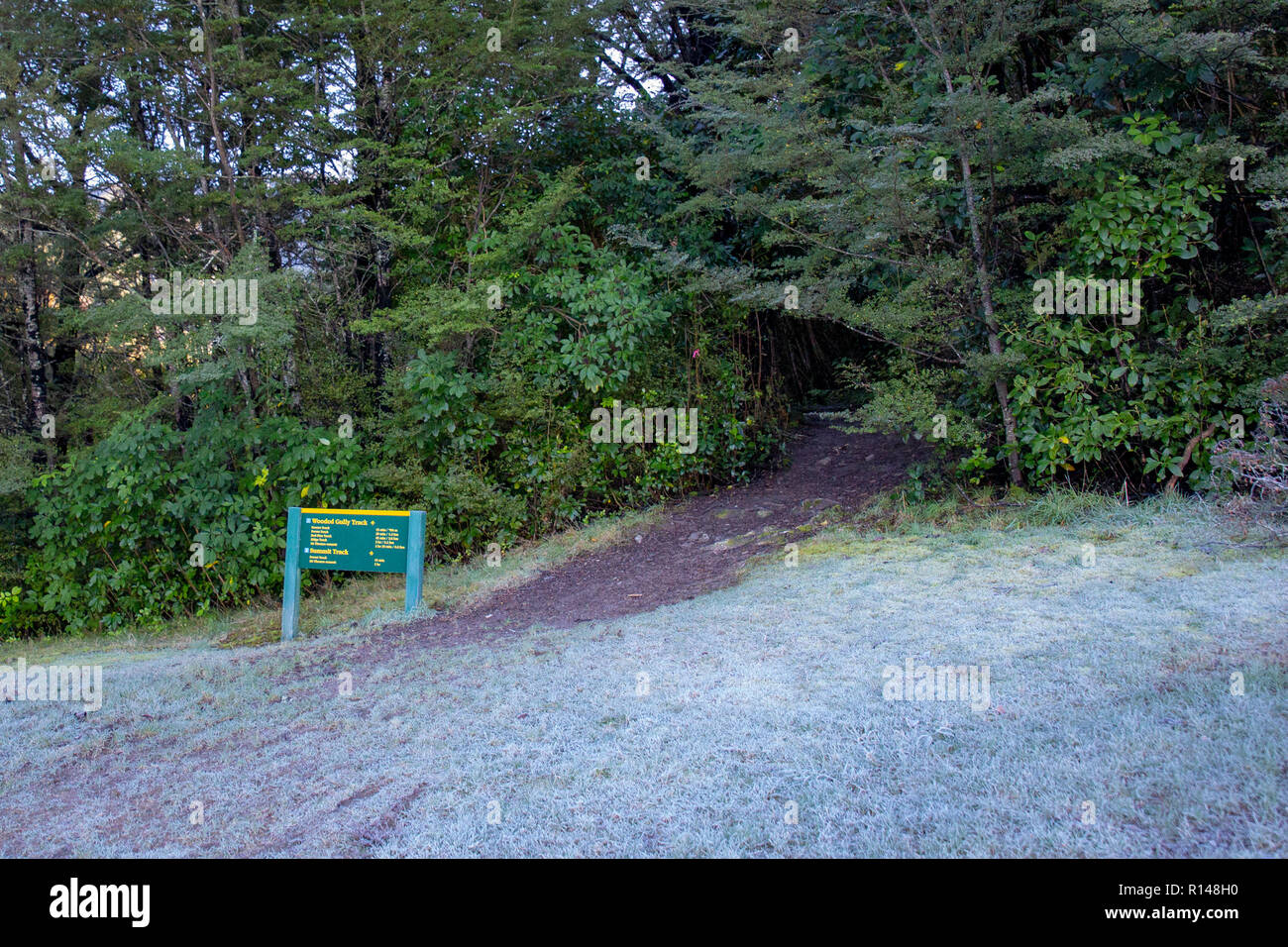The start of a hiking track or trail with winter frost on the ground - Stock Image