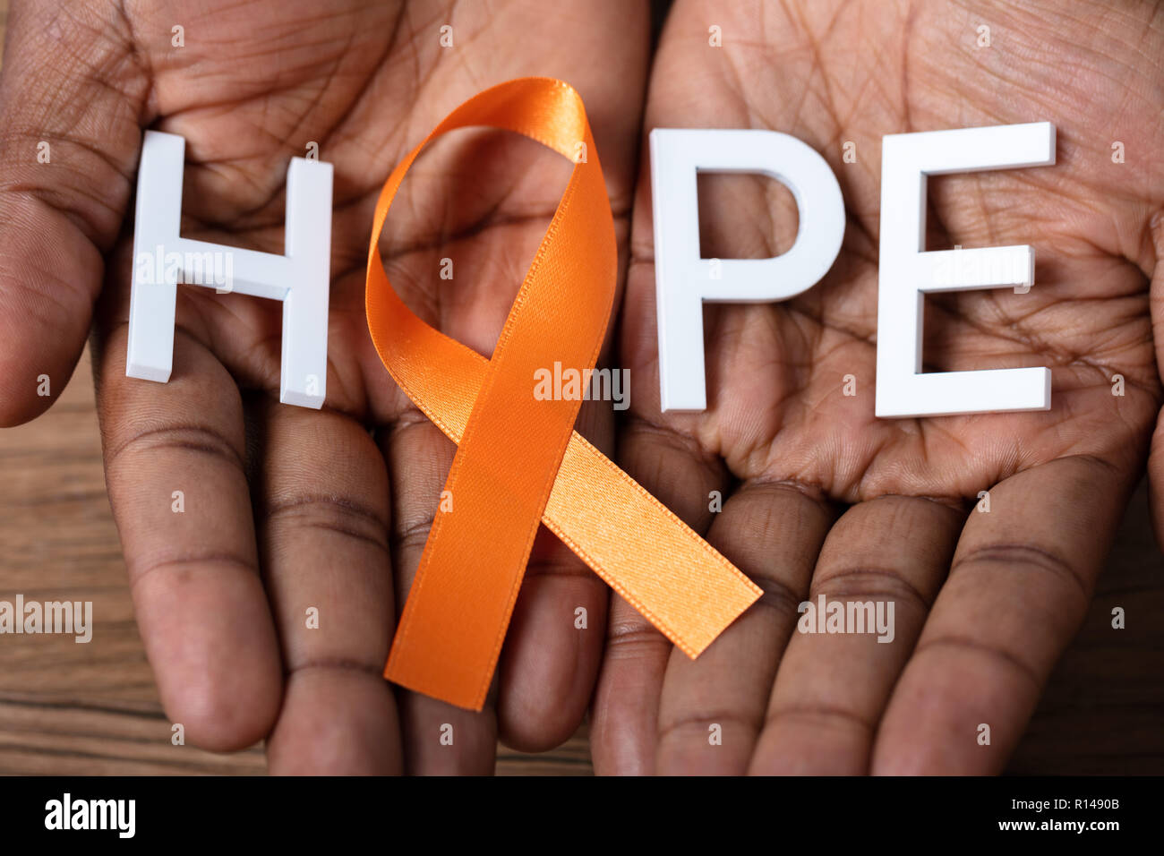 Person's Hand Holding Ribbon With Hope Text To Support Kidney Cancer And Leukemia Awareness - Stock Image