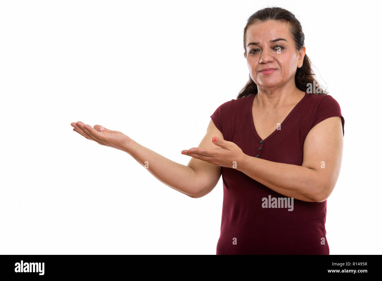 Studio shot of mature Persian woman showing something - Stock Image