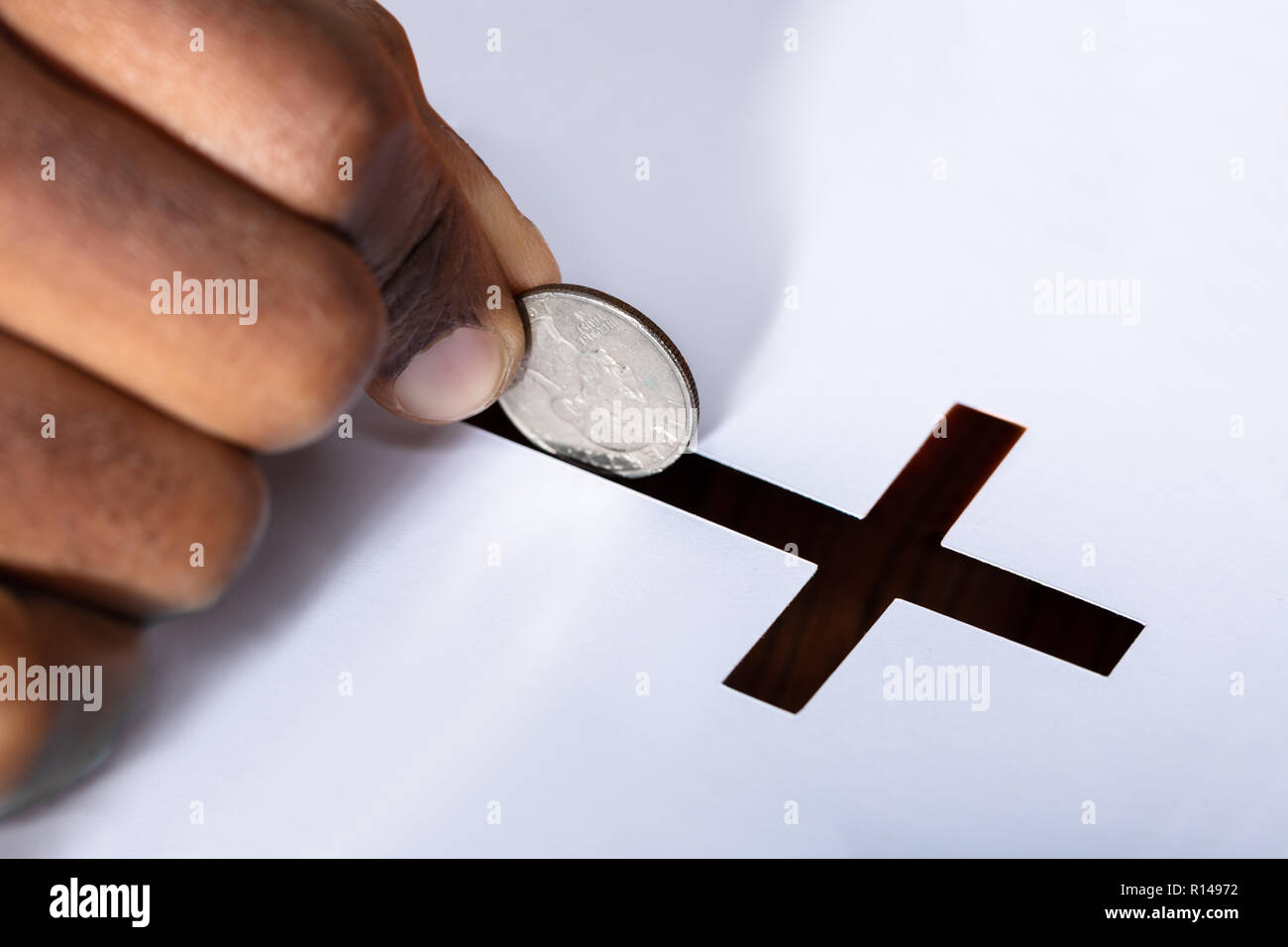 Close-up Of A Person's Hand Inserting Coin In Crucifix Slot Stock Photo