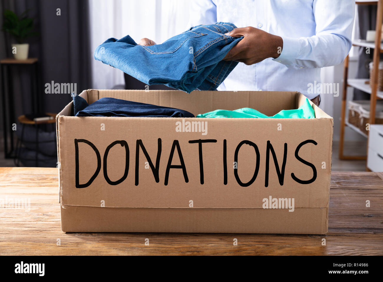 African Man Putting Clothes In Donation Box - Stock Image