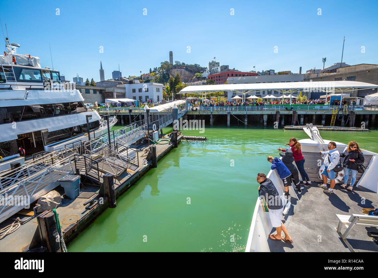 San Francisco, California, United States - August 14, 2016: Alcatraz Flayer cruise in pier 33 with tourists. San Francisco skyline on background. Blue sky. - Stock Image