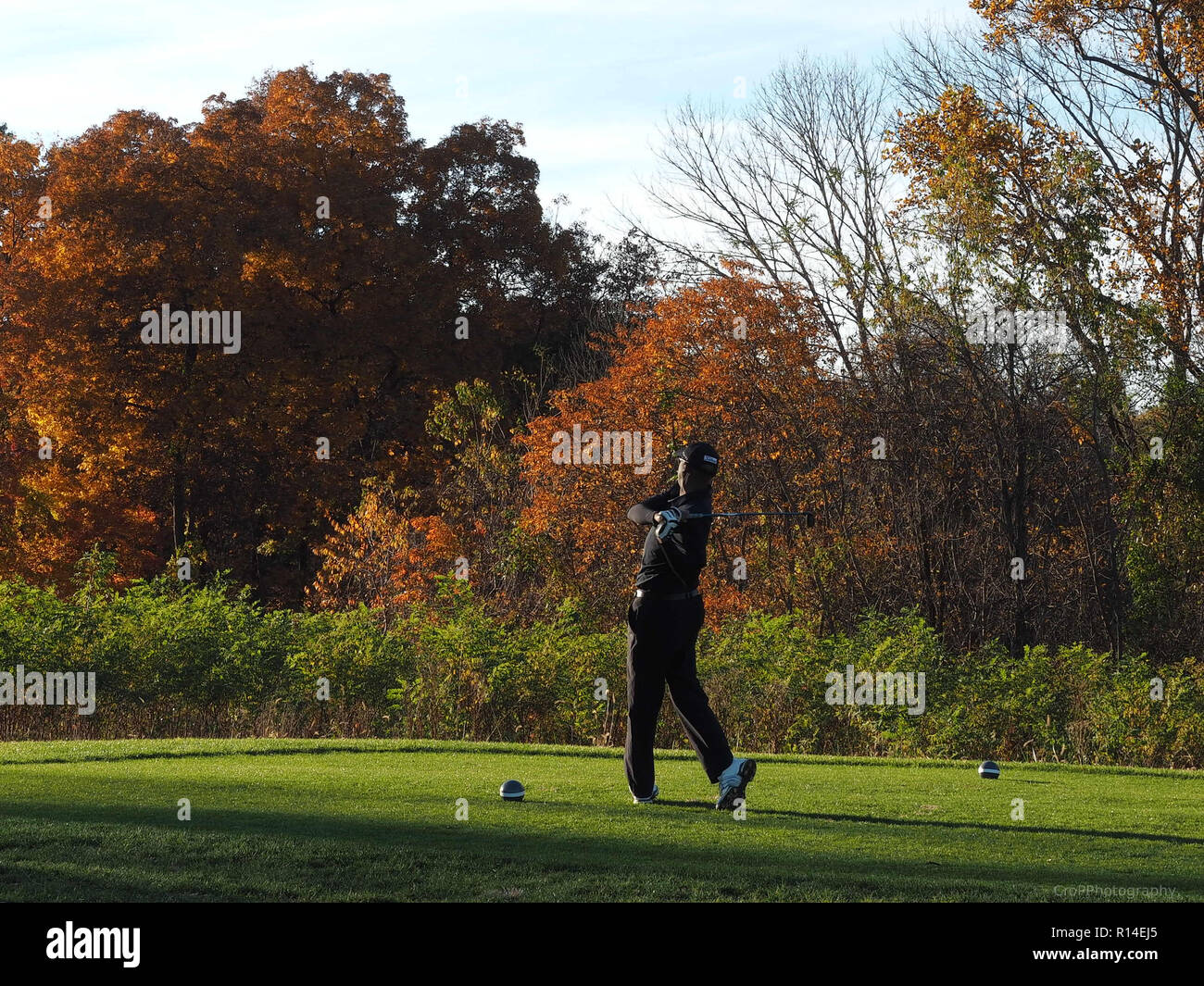 Golfer follow though swing on tee box in the fall - Stock Image