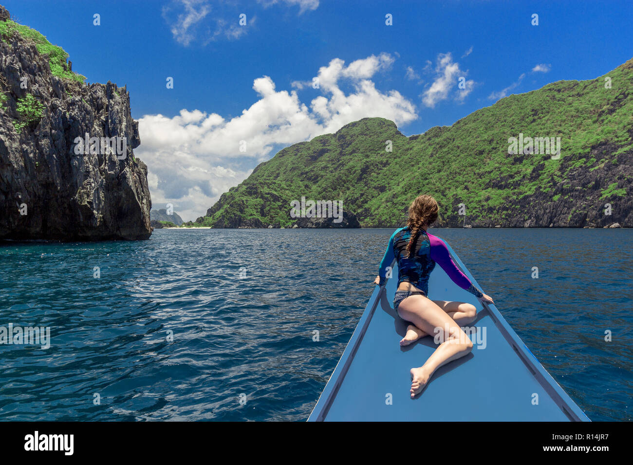Back view of the young woman relaxing on the boat and looking at the island. Travelling tour in Asia: El Nido, Palawan, Philippines. - Stock Image