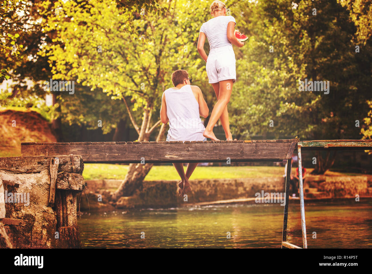 couple in love enjoying watermelon while sitting on the wooden bridge over the river in beautiful nature Stock Photo