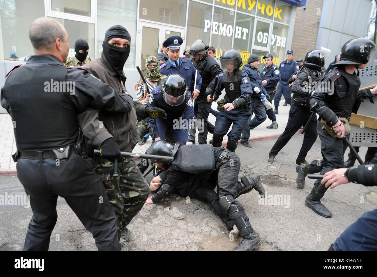 "April 28, 2014 - Donetsk, Ukraine: An Ukrainian riot police officer dives on a pro-Ukraine demonstrator in order to protect him from his pro-Russia aggressors.Pro-Russia militants attacked Ukrainians who demonstrated peacefully for the preservation of the unity of their country. The pro-Russian separatist group, mostly youths in balaclava, then celebrated their actions by screaming they had smashed ""the fascists"". Une manifestation pacifique en faveur de l'unite de l'Ukraine a Donetsk est brutalement dispersee par des groupes separatistes pro-russes armes de batons et, pour certains, d'armes b Stock Photo"