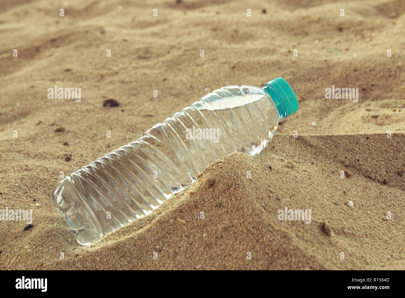 Bottle of clean drinking water in a dry desert, copy space. - Stock Image