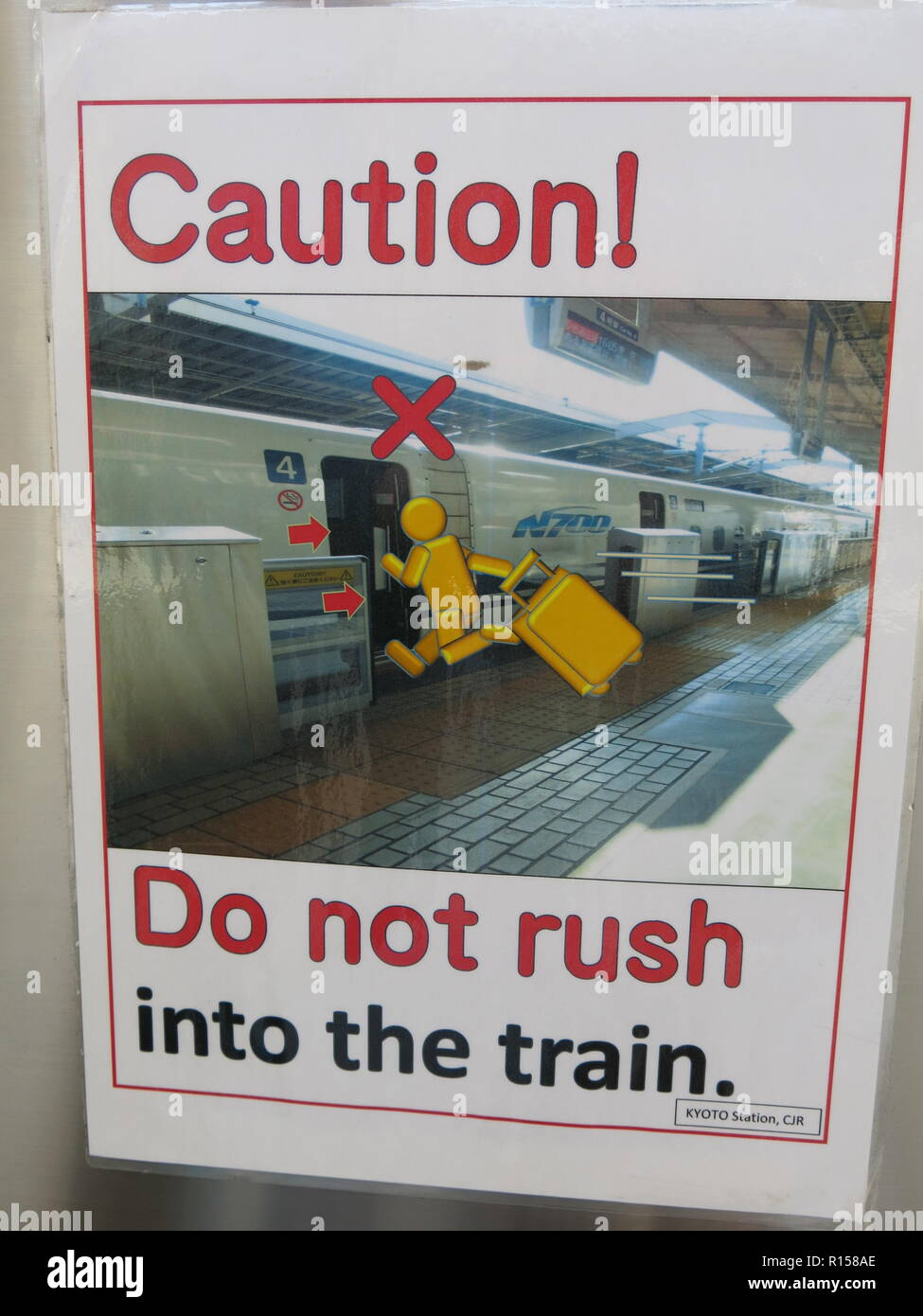 Photo of the poster at Kyoto railway station for the Japanese Bullet train: 'Caution! Do not rush into the train' - Stock Image