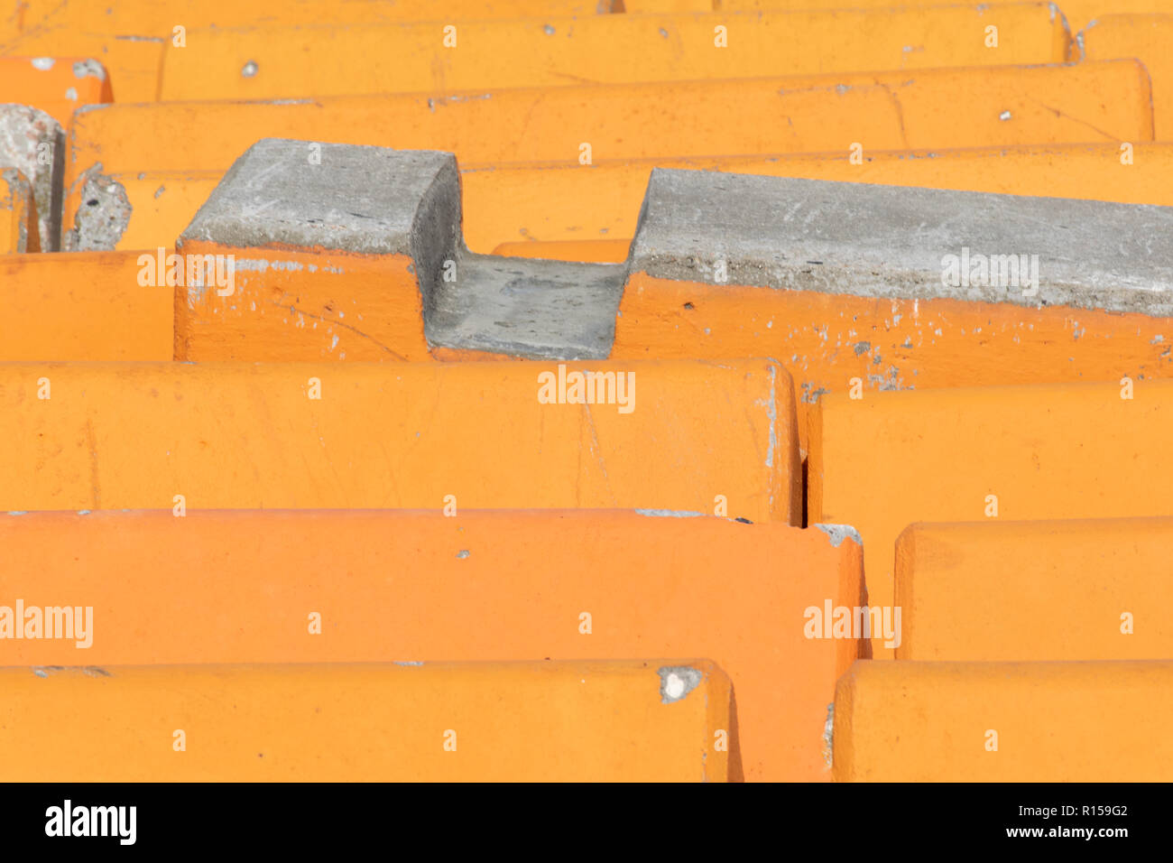 Close up detail of orange concrete road barriers used to line streets protecting pedestrians from terrorist attack using motor vehicles. - Stock Image