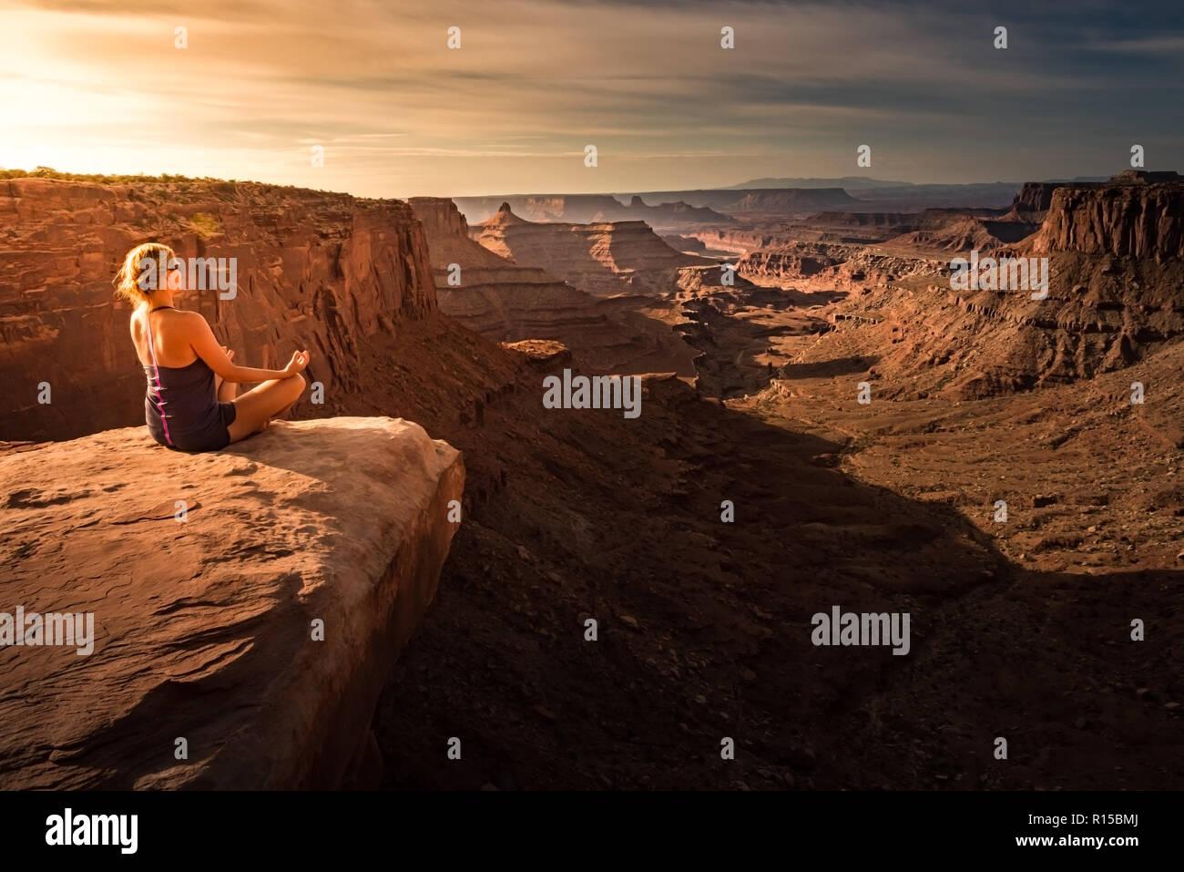 Woman practicing yoga meditation at Sunrise. Beautiful Canyonland Landscape - Stock Image